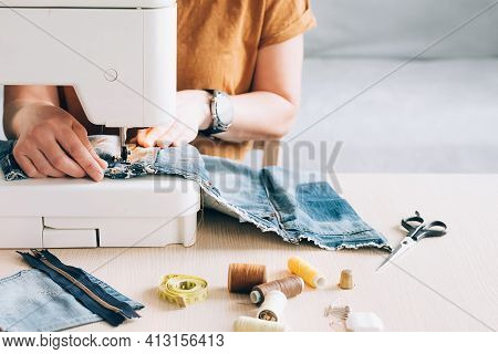 A Woman Tailor Works At Sewing Machine Sews Reuses Fabric From Old Denim Clothes