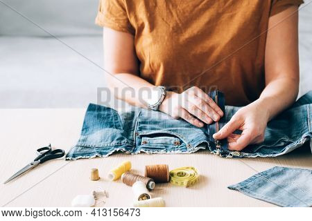 Woman Repairs Sews Reuses Fabric From Old Denim Clothes Economical Reuse