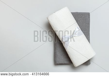 Top View Of A Stack Of Rolled Up White And Gray Towels With Copy Space.