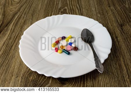On The Wooden Table Is A White Plate With Tablets.