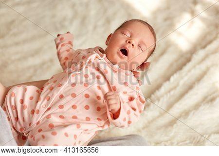 Sleeping Newborn Baby In Mother Hands, Cute Kid Wearing Sleeper With Polka Dots, Kid Keeps Mouth Ope