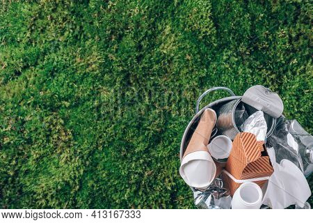 Plastic Waste, Food Packaging In Trash Bin Trash Collection On Green Moss Background After Picnic In