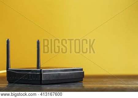 Black Wi-fi Router On A Yellow Background With Free Space.