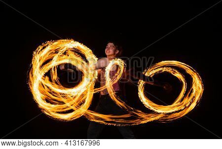 Happy Male Fire Dancer Twirl Burning Baton Creating Sparkling Trails In Motion Dark Outdoors, Twirle