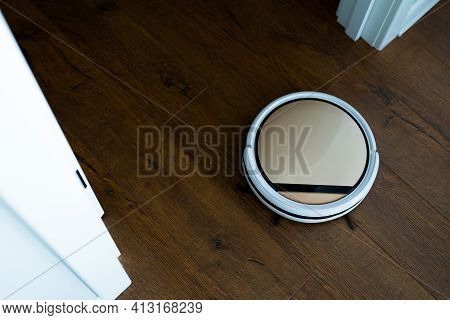 Photo From Above. A Remote-controlled Vacuum Cleaner Moves Across The Parquet Floor