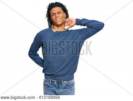 Young african american man wearing casual winter sweater suffering of neck ache injury, touching neck with hand, muscular pain