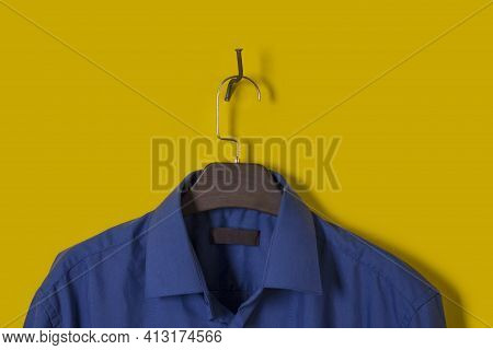 Blue Mens Shirt On Brown Plastic Hanger On Yellow Background With Copy Space. Concept Store, Sale, D