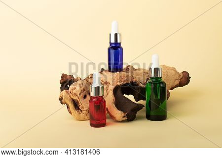 Cosmetics Bottles From Multicolored Glass With Droppers Staying On The Tree Bark.pleasant Pastel Ban