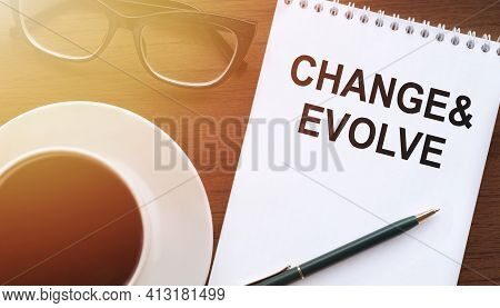 Change And Evolve - Text On Paper With Cup Of Coffee And Glasses On Wooden Background In Sinlight.