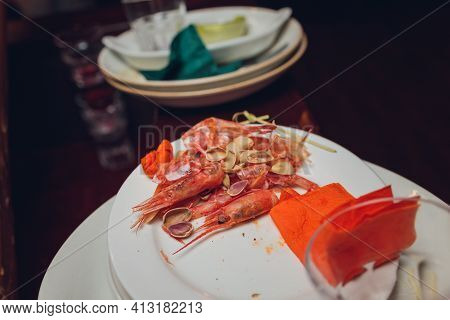 A Plate With A Fork And A Knife Stands With Leftovers And Leftovers. Delicious Dinner With Seafood F