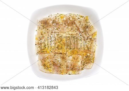 A Fresh Cod Fish Fillet Cut Into Squares, Sprinkled With Spices Lying On A White Plate, Isolated On