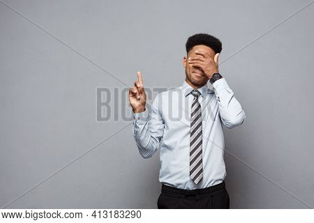 Business Concept - Confident Thoughtful Young African American Pointing Finger On Side Over Grey Bac