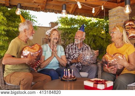 Group Of Cheerful Senior Friends Celebrating Friends Birthday, Wearing Party Hats And Holding Balloo