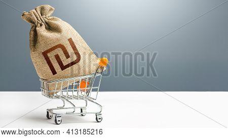 Israeli Shekel Money Bag In A Shopping Cart. Public Budgeting. Profits And Super Profits. Business A