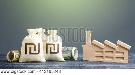 Israeli Shekel Money Bags And Industrial Factory. Investments In Production And Energy Industry. Sub