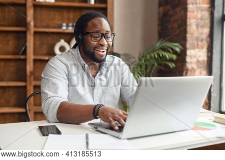 Focused African American Businessman In Eyewear Wearing Headphones, Holding Video Call With Clients