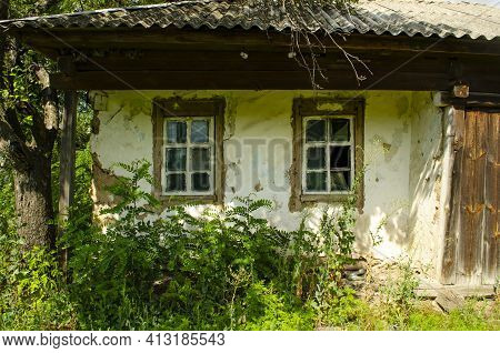 Old Wooden Rustic House Plastered With Clay And Painted With White Clay Among Flowering Meadow Grass