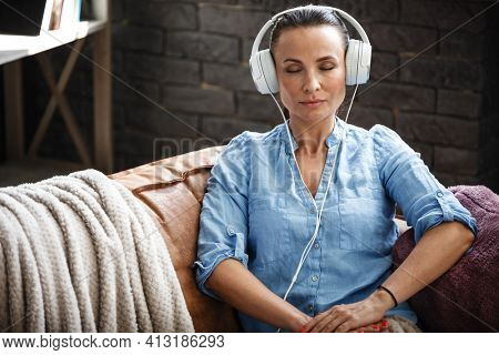 Leisure time concept. Happy beautiful woman listening to the music using headphones sitting on a couch indoors. Female spending her free day and relaxing at home alone