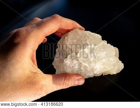A Hand Holding Shiny Transparent White Halite Rock Salt Mineral Crystal From Soligorsk, Belarus, In