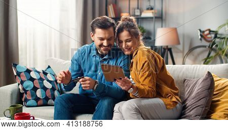 Cheerful Happy Young Caucasian Married Couple Man And Woman Buying Online Typing On Tablet Paying Wi