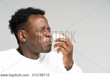 Unhealthy African American Man Blowing Nose And Sneeze Into Tissue Or Napkin, Experiences Allergy Sy