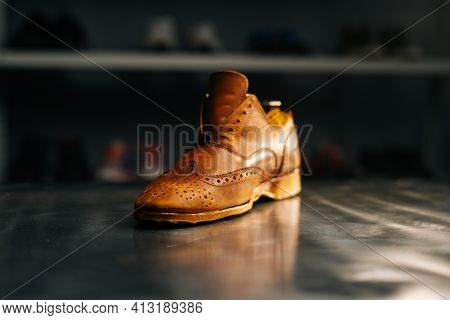 Close-up Side View Of Old Light Brown Leather Shoes With Wooden Shoe Pad To Be Repaired In Dark Craf