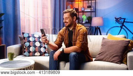 Cheerful Caucasian Handsome Young Male Speaking On Video Call Online On Smartphone Sitting On Couch