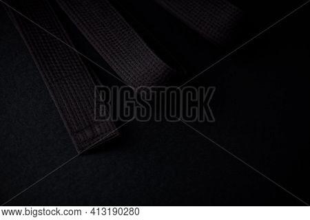 Black Karate (judo) Belt On Dark Background. Close Up. Copy Space.