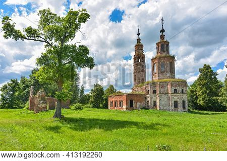 An Abandoned Dilapidated Church, Overgrown With Grass Against The Background Of The Sky, Surrounded