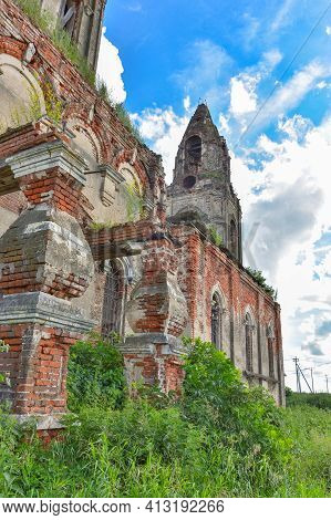 Part Of A Ruined Church With A Bell Tower Overgrown With Grass Against The Background Of A Cloudy Sk
