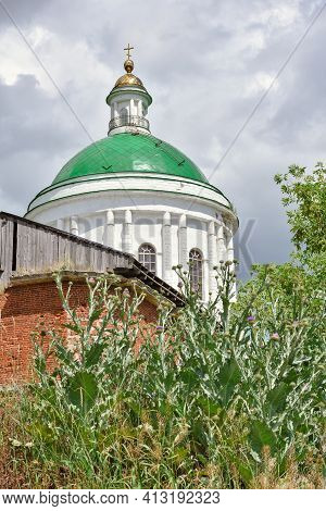 Part Of A Restored Church With A New Dome Against A Cloudy Sky, Surrounded By Greenery, Close-up