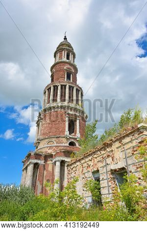 An Abandoned Brick Bell Tower With Columns, A Cross And Part Of A Destroyed Wall Overgrown With Gree