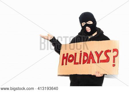 Thief Wearing A Ski Mask Showing A Cardboard Sign On Which The Word