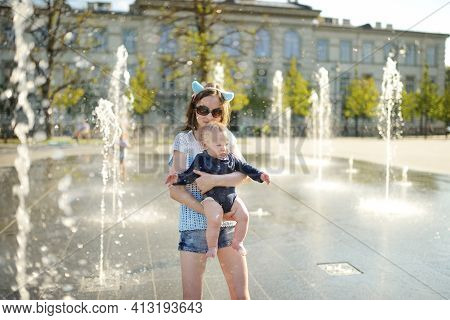 Cute Big Sister Holding Her Baby Brother By City Fountain. Adorable Teenage Girl Playing With Her Ba