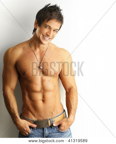 Sexy portrait of a young muscular male model with great happy smile against white wall