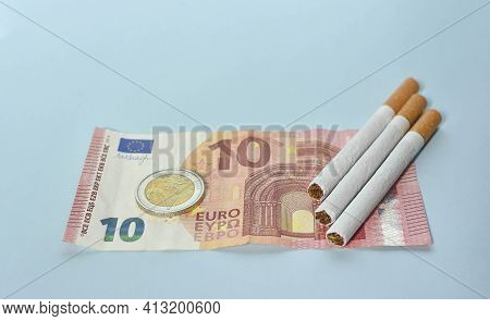 Cigarettes And Money On Blue Background. Euro Banknotes And Coins, Cost Of Smoking, Cigarette Price