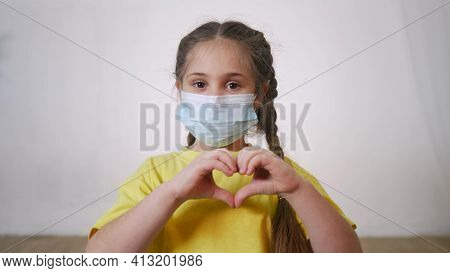 Face Child Protective Mask Shows A Gesture Heart. Stay Home Coronavirus Quarantine Kid Dream Concept