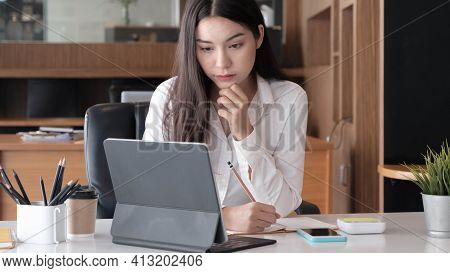 Photo Of Cheerful Joyful Asian Woman Writing Down Notes Holding Tablet For Data Analysis