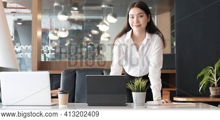 Confident Businesswoman Standing At Her Office Desk And Smiling To Camera.