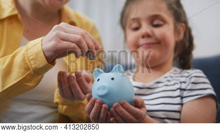 Happy Family Piggy Bank. Mom And Daughter Future A Put Coins In The Piggy Bank. Mortgage Loan Saving