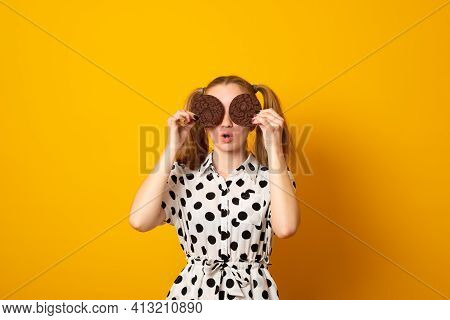 Full Of Sweet Chocolate Flavors. Cute Girl Having Fun With Cookies. Pretty Girl Covering Eyes With C