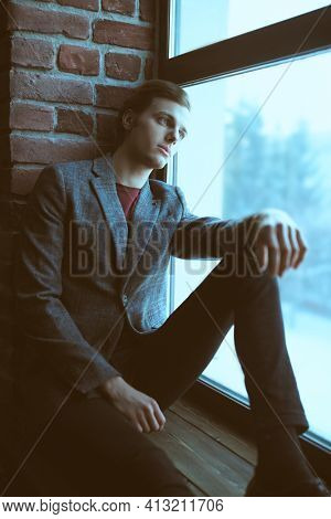 A handsome guy in casual clothes dreamily looks out the window sitting on the windowsill.