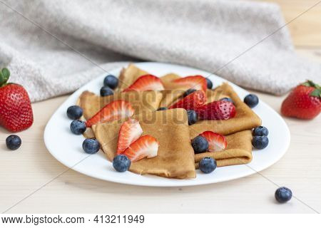 Pancakes With Blueberries And Strawberries On The Table. Traditional Food For Maslenitsa