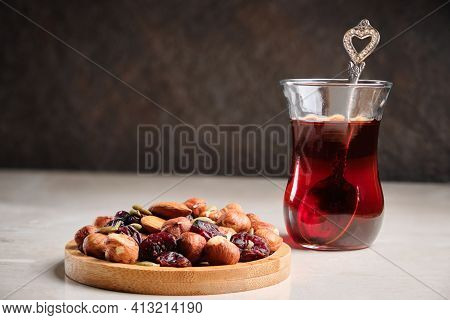 Turkish Tea In Traditional Tea Glass And Mix Of Hazelnuts, Almonds, Raisins And Other Nuts At Bright