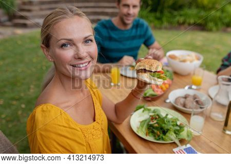 Portrait of smiling caucasian woman holding hamburger eating meal with family in garden. family celebrating independence day eating outdoors together.