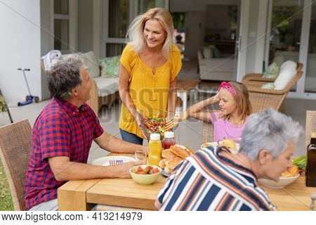 Smiling caucasian woman serving family before eating meal together in garden. three generation family celebrating independence day eating outdoors together.