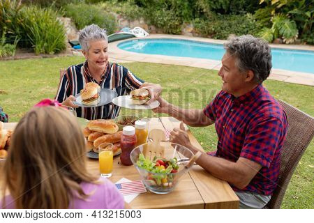 Smiling caucasian senior man serving family before eating meal together in garden. three generation family celebrating independence day eating outdoors together.