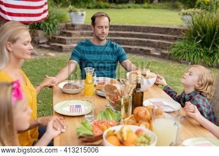 Caucasian man and family holding hands saying grace before eating meal together in garden. family celebrating independence day eating outdoors together.