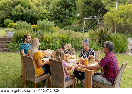 Caucasian three generation family holding hands saying grace before eating meal together in garden. three generation family celebrating independence day eating outdoors together.