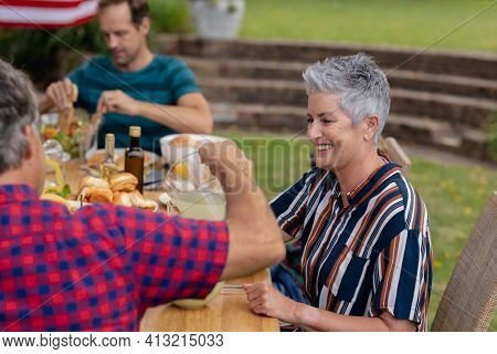 Smiling caucasian senior woman sitting with family eating meal together in garden. three generation family celebrating independence day eating outdoors together. with